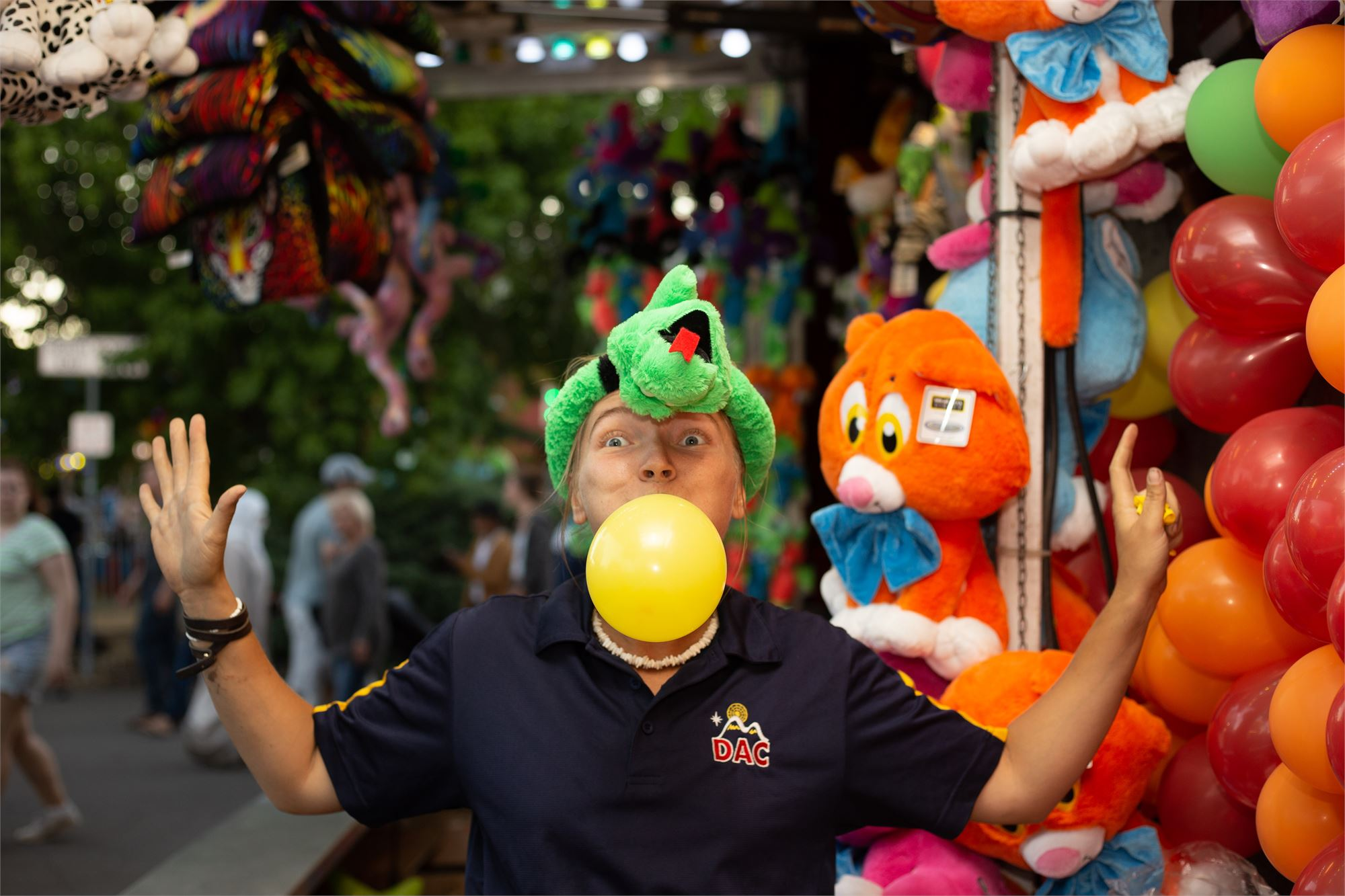 Carnival Worker at game booth having fun blowing up a balloon with no hands