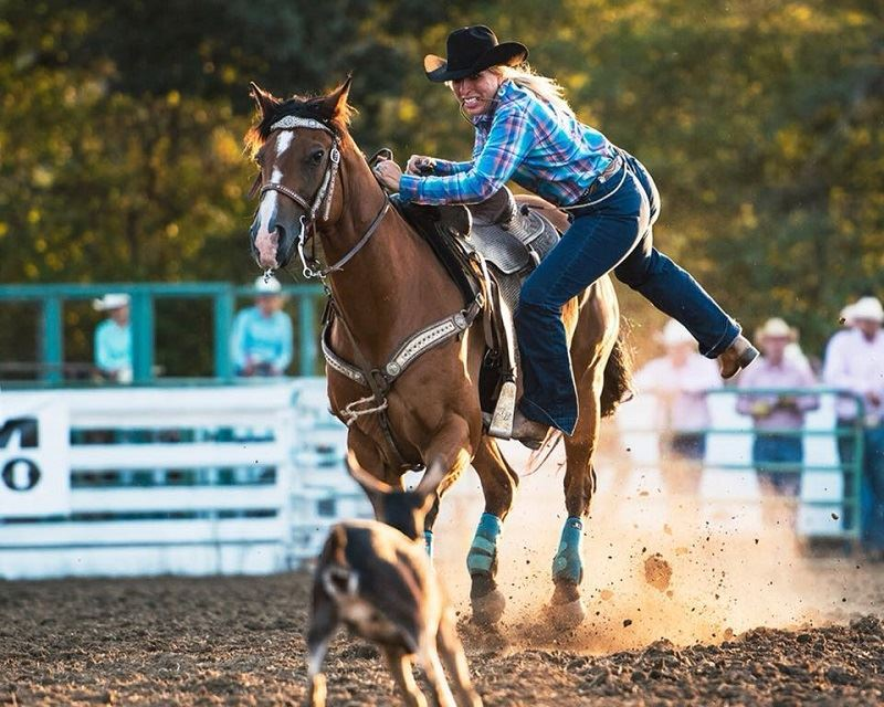 Photo: Cowgirls jumping off her horse to tie down a goat