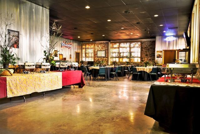Inside of the Boot Daddy Saloon with a buffet set up and round tables with black linens.