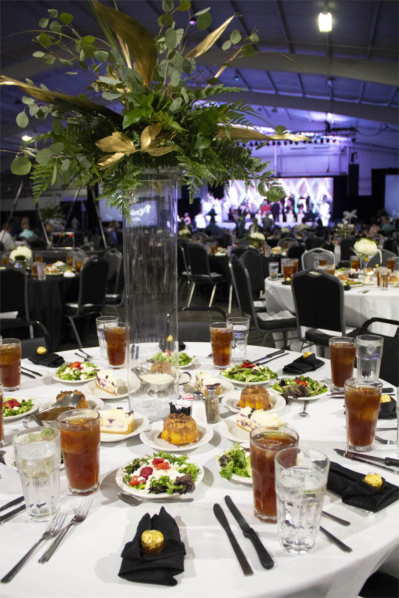 Inside E*Plex Hall with over 150 round tables set up with large flower arrangements. In the background is a large screen and stage.