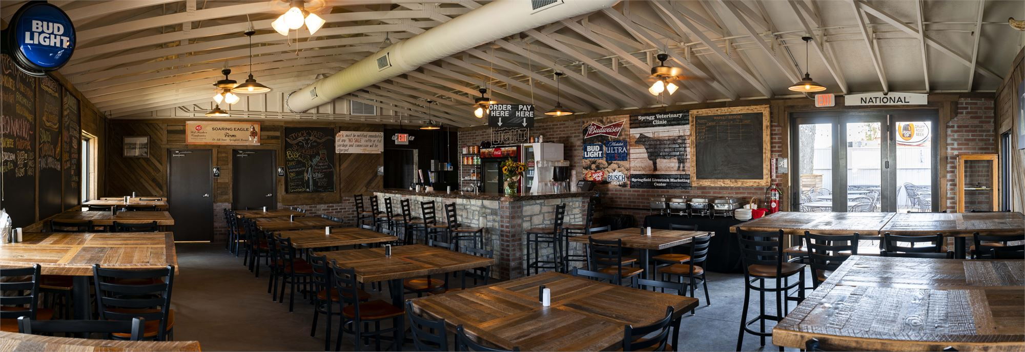Inside of the Stockyard Smokehouse with handmade tables and a large wooden bar.