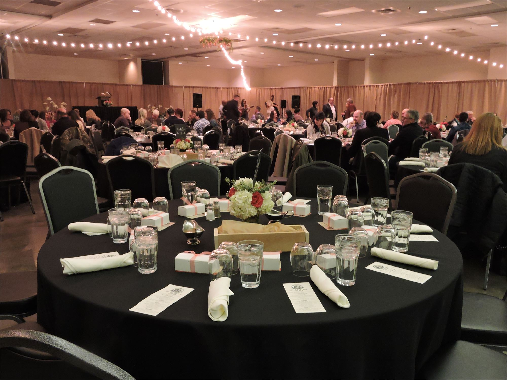 Inside of Center Hall with round tables with black linens set up and pink organza fabric draped over the ceiling with string lights