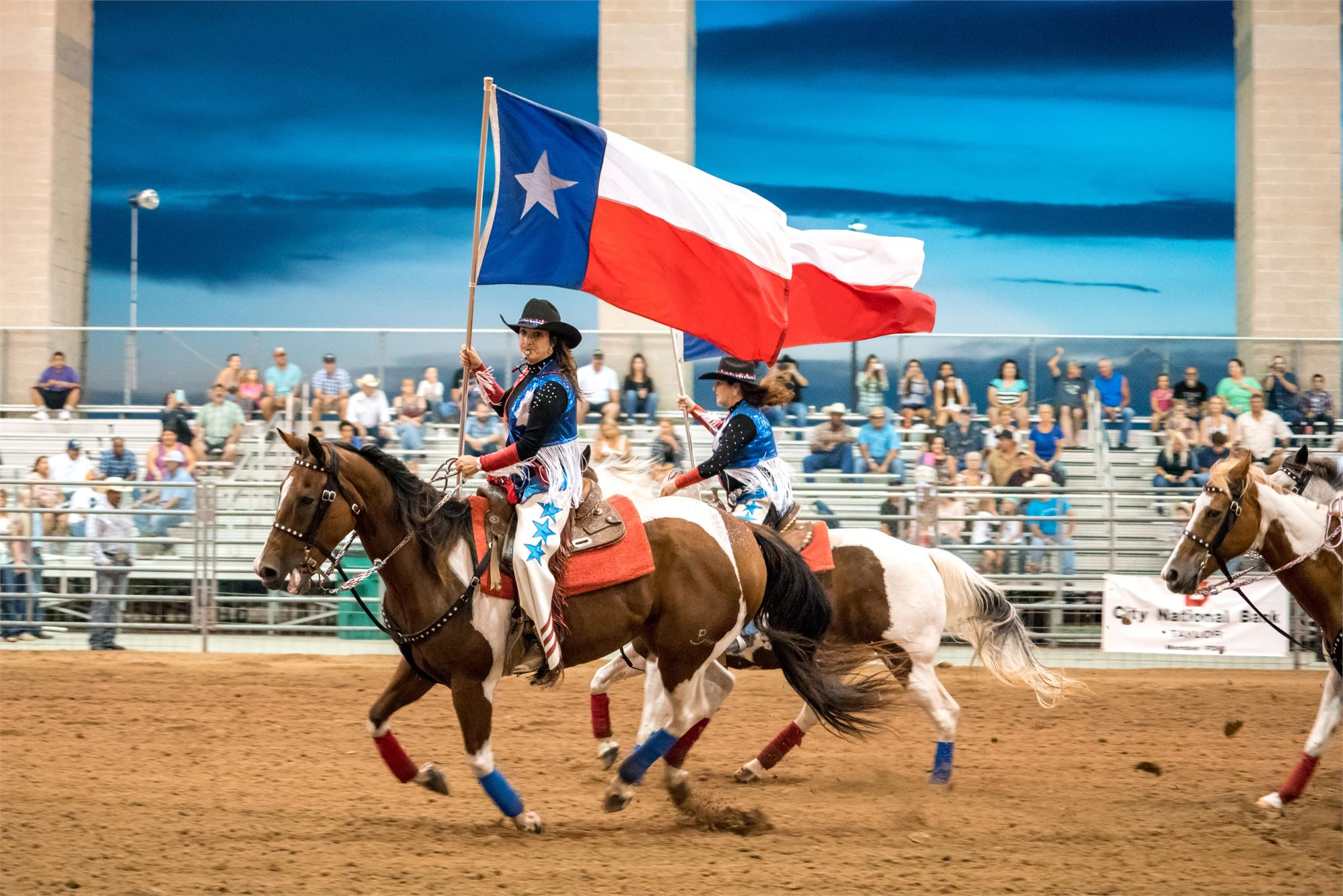 Cowgirls riding through the arena with Texas Flag during the Taylor Rodeo at night