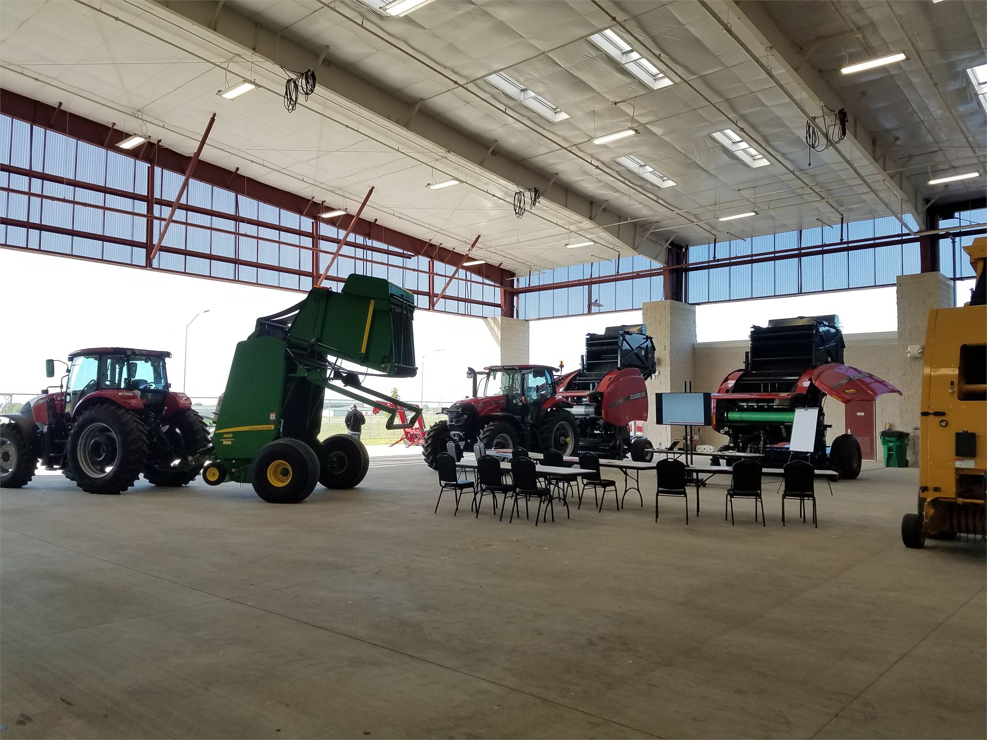 Covered expo with four tractors and other farm equipment setup for a demonstrastration