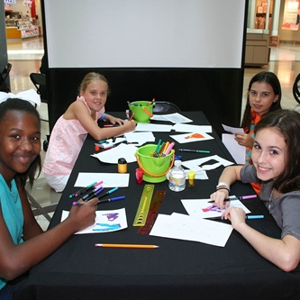 Four girls drawing on paper